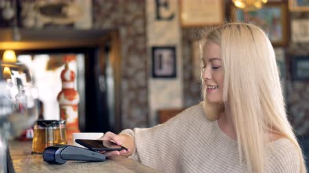 nfc : A young woman makes a contactless payment and waves to someone. Stock Footage