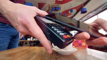 scanning : An NFC payment process shown in a coffee shop. Stock Footage