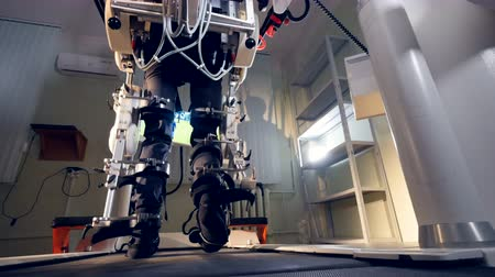 futuristic concept : Male feet walk inside an exoskeleton in a back view.