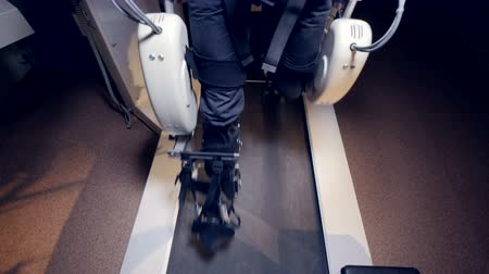 dangle : Male feet in an exoskeleton move above a treadmill.