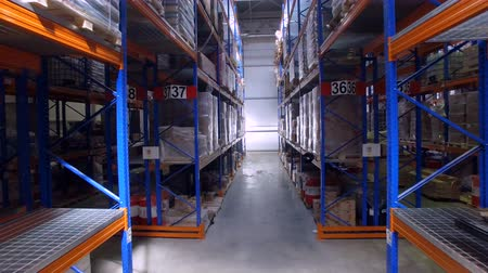 stockpile : Dim low levels of warehouse racks in different aisles.