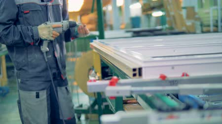 csavarhúzó : Worker manufacturing plastic window. Assembly line of PVC windows and doors.