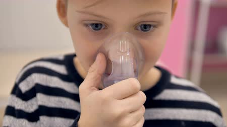 lung : A close-up view on a boy using an inhaler mask.