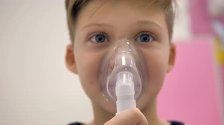 inhalacja : A close-up on a boys face hidden by an inhaler mask.