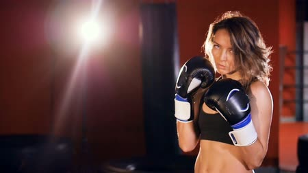 actively : Strong woman in a boxing stance. Slow motion.