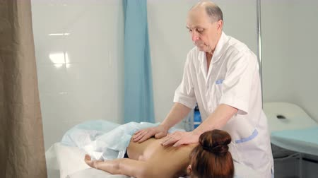 masażysta : The massage therapist is massaging womans back