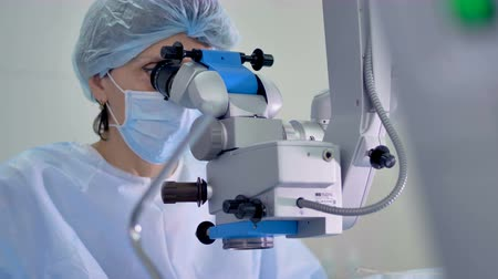 glaucoma : A female surgeon uses a profession microscope station. Stock Footage
