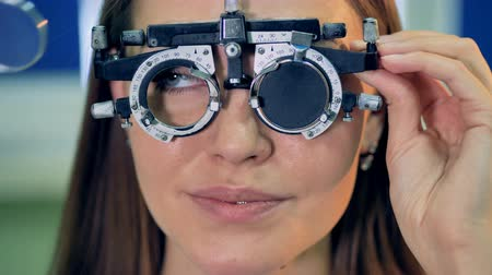 optyk : A woman approves a lens and removes her trial frames.