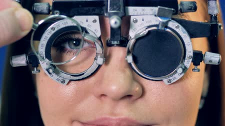 düzeltme : A doctor changes lenses inside a womans trial frame. Stok Video