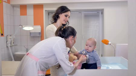 incelenmesi : Doctor play with baby on treatment table in clinic.