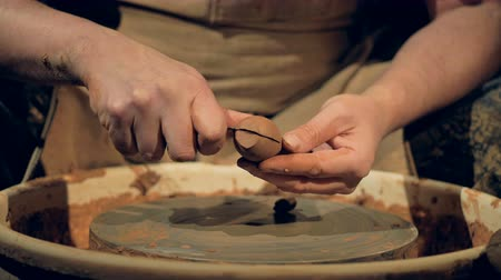 excesso de trabalho : A potter cuts off excess clay from a spoon workpiece.