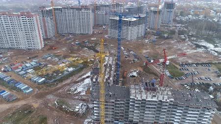 andaime : A camera zooming in on working construction cranes.