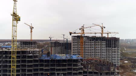 аналогичный : Several grey concrete buildings with unfinished higher floors.