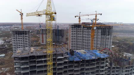 identical : A yellow tower crane on a construction site with many buildings.