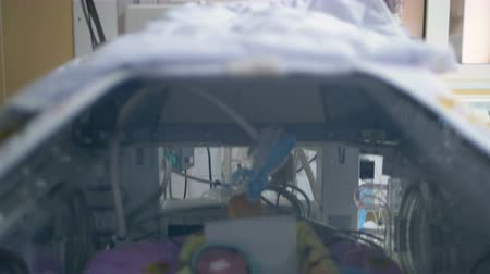 intensive care unit : Screens with newborns vitals above an ICU incubator.