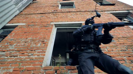 armed : Special unit soldiers exit a building after their operation. Stock Footage