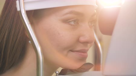 tests : A woman places her head on medical equipment supports before an eye exam. 4K. Stock Footage