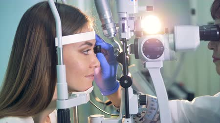 optyk : An ophthalmologist confirms good results to a woman during a test.
