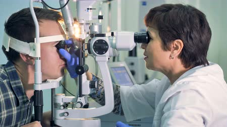 katarakt : An ophthalmologist in her office checks the man for eye injuries. Stok Video