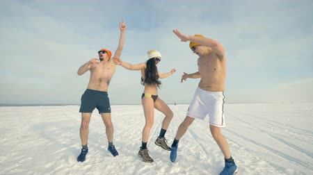 snowboarder : Two men and a woman in bikini dance on the snow. 4K. Stock Footage
