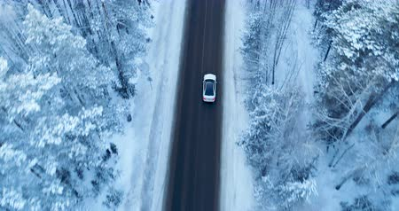 nordic countries : Aerial view on a car driving on winter country road in snowy forest.