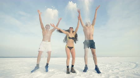 raised : Three friends play with winter snow while wearing swimsuits.