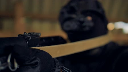 sniper scope : A focused shot of a SWAT members rifle with the barrel pointed at target. Stock Footage