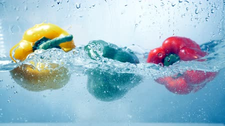 capsicum : A closeup on three peppers falling inside water. Stock Footage