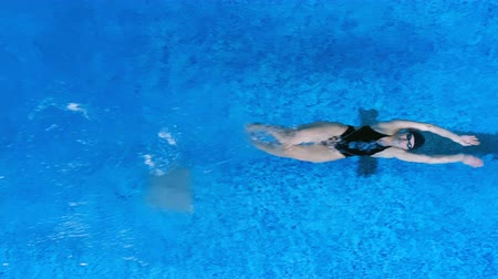 submerge : A swimmer moves on her back underwater before moving up.