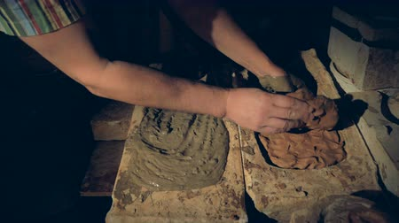 oleiro : Potters hands remove a half dry slab of clay from the mold.