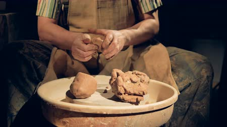 глыба : Potters hands work on several large lumps of crude clay.
