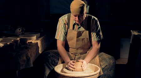 holding onto : A potter presses a large clay ball onto a pottery wheel.