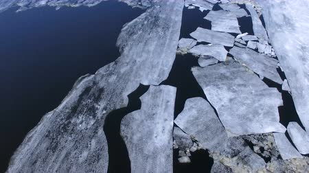 período : Large ice slabs floating in the middle of the river.