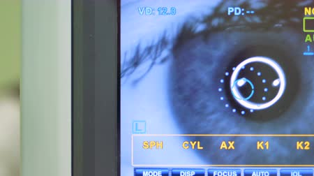 optometria : A modern autorefractometers screen showing as blinking human eyes get tested. 4K.