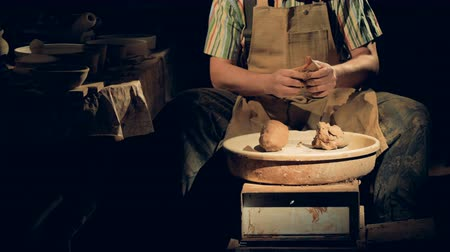 глыба : An unrecognizable potter in a dark studio kneads clay. Стоковые видеозаписи
