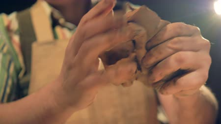 otisk : A low view on potters fingers pressing into clay to knead it.