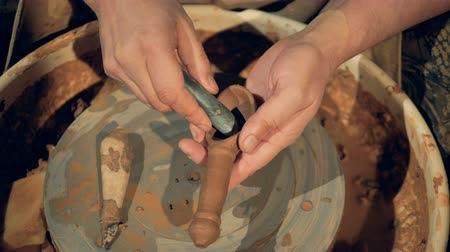 oleiro : A potter uses a rounded stone to polish inside a clay spoon. Vídeos
