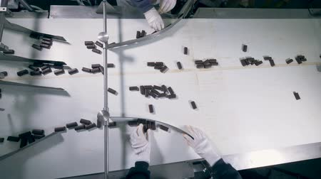 sorted : Two pair of hands are sorting chocolate candies on the conveyor belt from a top view 4K.