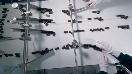 üreten : Plenty of chocolate candies are going along the conveyor belt and getting sorted Stok Video