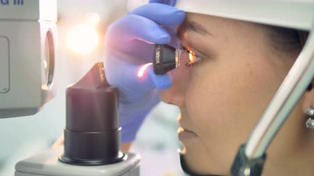professionalism : Close up of womans eye getting examined by an ocular in doctors hand Stock Footage