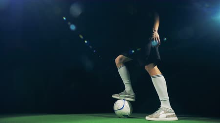 stockings : Professional soccer player is rushing into the picture and getting the ball.