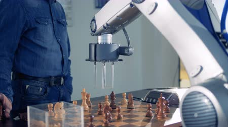 mozek : Innovative gaming emulator, robot playing chess with a human. Futuristic robotic concept.