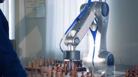 робот : Man playing chess with innovative robotic chess artificial intelligence.