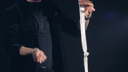 varázsló : Magician makes two knots disappear from a white tie.