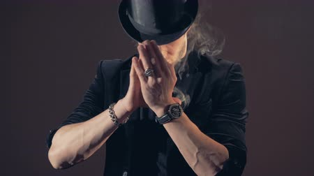 büyücü : Magician is standing, his hands folded near his face, with smoke appearing. Stok Video