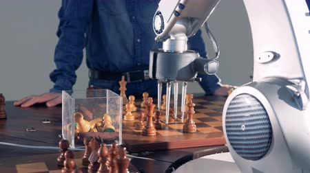 versengés : Robot and human competition. Robot hand playing chess with a man. Artificial intelligence concept. 4K.