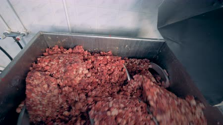 tuned : Small pieces of meat are getting dropped from a container to a working stirring machine