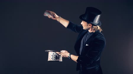 travessura : A male illusionist is performing magic tricks with cards and putting them together into a card top hat Vídeos