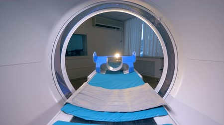 tomograph : An empty patients cot moves inside a CT scanner.