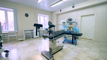 helpful : Side view of an obstetrics hospital room with professional equipment and examination chair